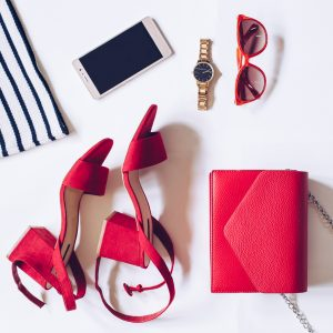 flat lay of a minimal set of female accessories:golden wrist watch, red mid heel sandals with ankle strap, clutch bag, mobile phone, sunglasses, striped shirt